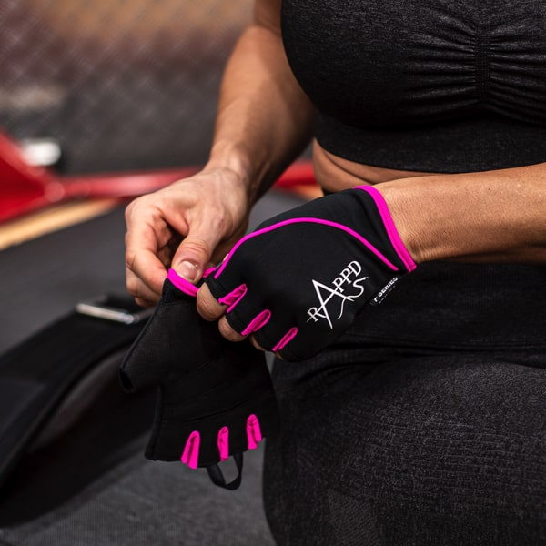 Woman putting on pink training gloves by Rappd