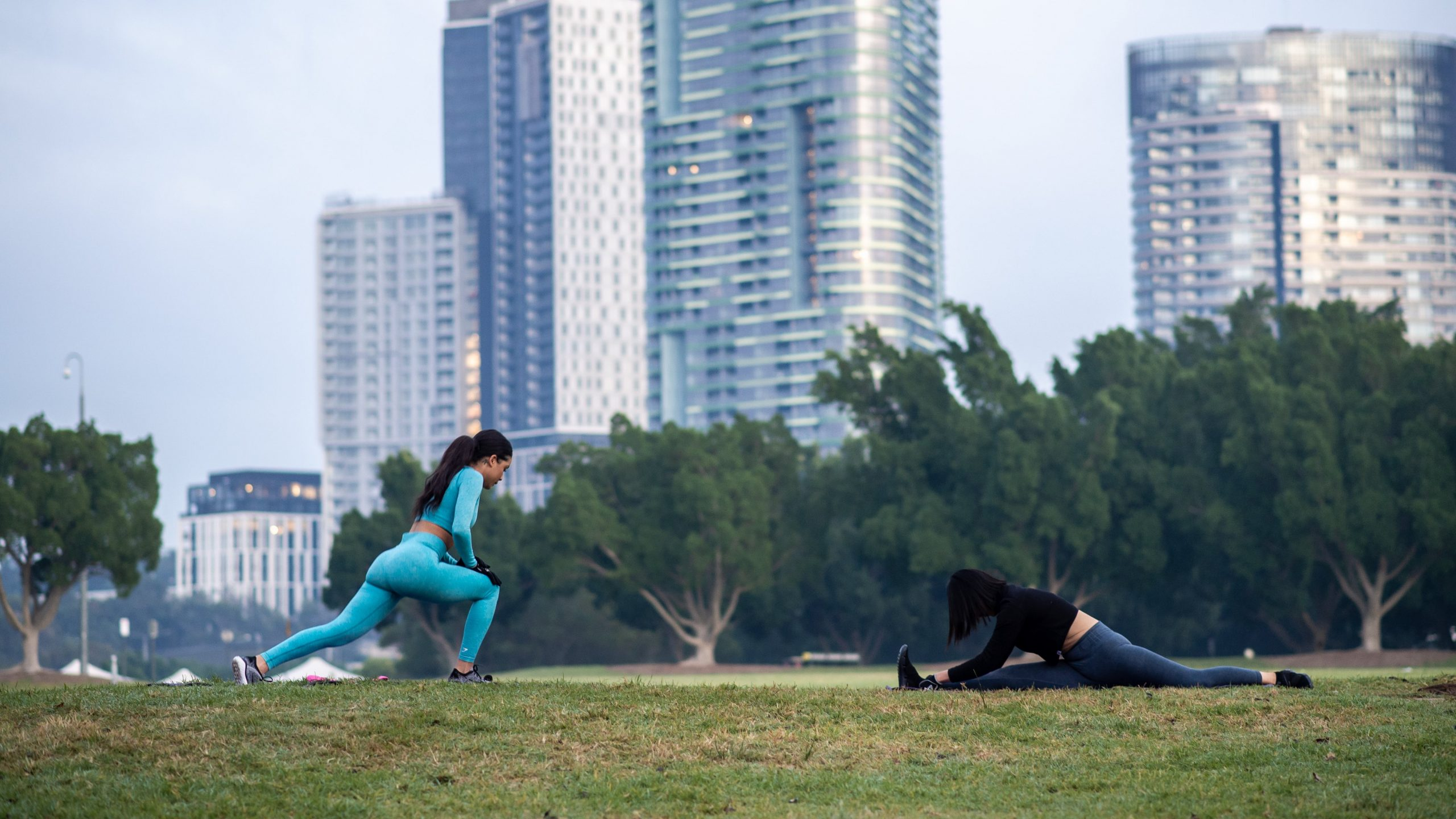 Two women exercising outside using gym fitness accessories