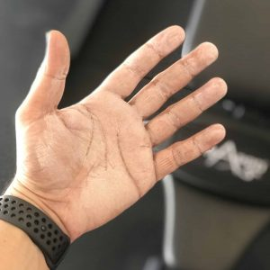 Inside of the palm of a man wearing liquid training chalk